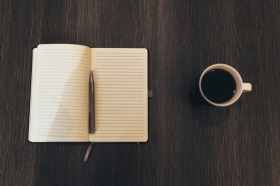 Open blank journal on a table with a cup of coffe