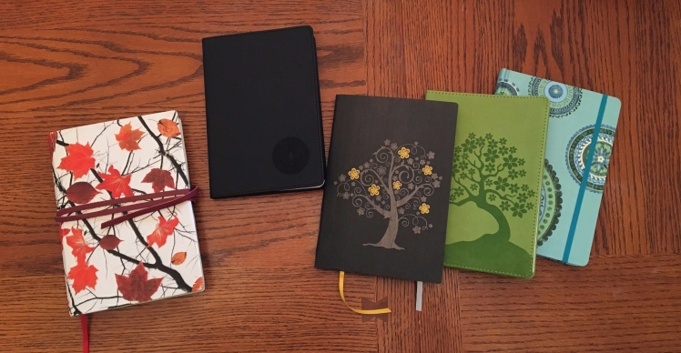 five journals on a wooden table
