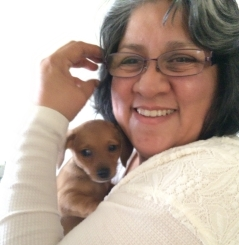 Hispanic woman wearing glasses holding a puppy