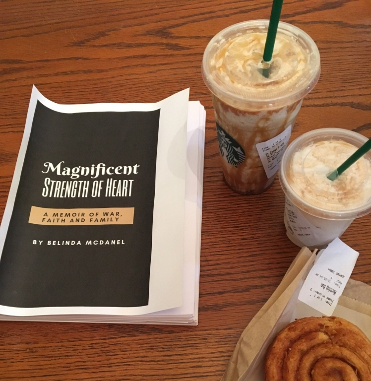 Next to two Starbucks drinks and a morning bun is the manuscript of a book. Title: Magnificent Strength of Heart: A memoir of war, faith and family by Belinda McDanel