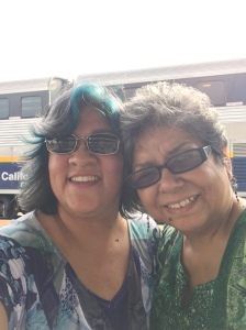 two hispanic women standing in front of a train